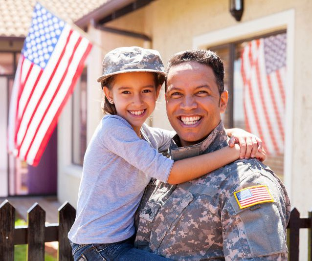 portrait of us army soldier and little daughter outside their ho